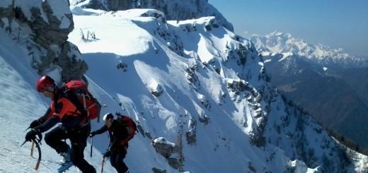 Alpinisti plezajo iz grap Laneža, zadaj Raduha in Kamniško-Savinjske Alpe